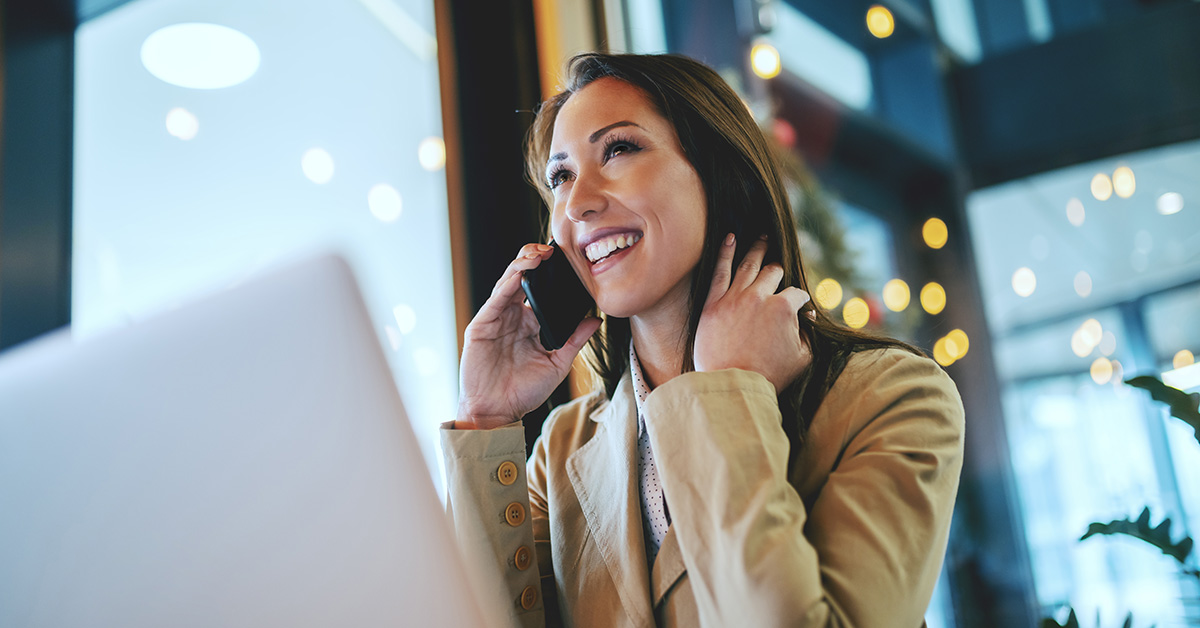 Photo of a happy woman on the phone in front of laptop